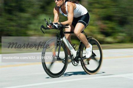 Woman riding road bike, cropped
