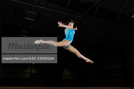 Teenage girl gymnast performing split leap, low angle view