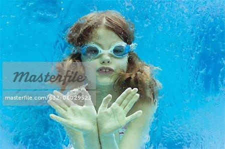 Girl wearing goggles swimming underwater in swimming pool