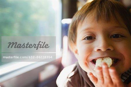 Boy eating chips, portrait
