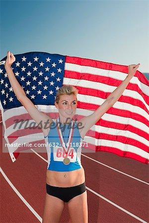 Female medal winner holding up American flag in victory