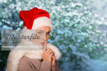 Woman wearing Santa hat, finger on lips, portrait