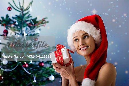 Woman wearing Santa hat, shaking Christmas gift