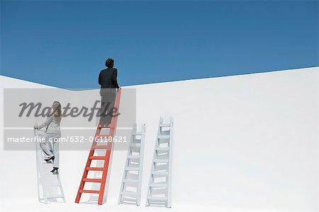 Businessman and businesswoman climbing ladders