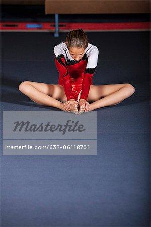 Gymnast sitting on floor stretching
