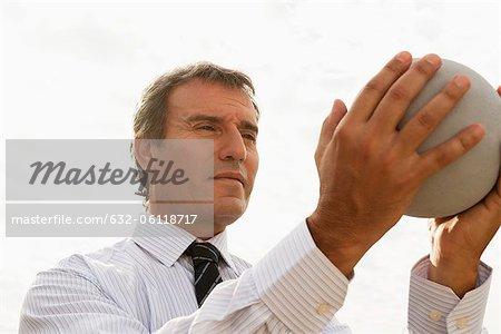 Mature man holding stone globe