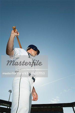 Baseball player holding baseball bat across shoulders