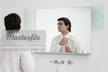Man adjusting shirt collar in mirror