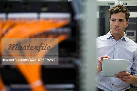 Computer technician using digital tablet performing maintenance check of mainframe equipment