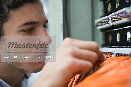 Computer technician performing maintenance work on networking equipment
