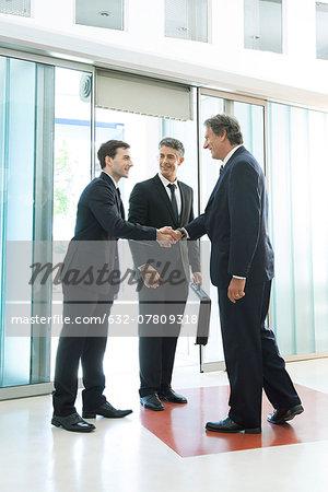Businessman meeting associates in office lobby