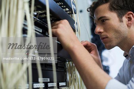 Computer technician performing maintenance on computer networking equipment