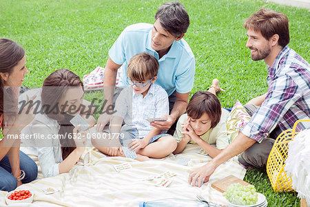 Family playing card game at picnic