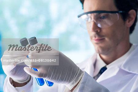 Scientist scrutinizing test tubes containing blue liquid in lab