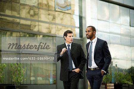 Businessmen walking and talking together