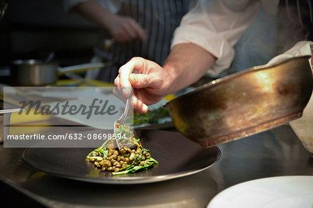 Chef spooning lentil dish onto serving plate