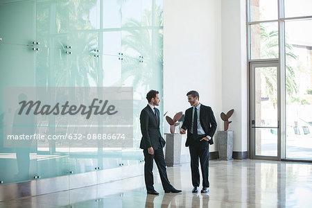 Business associates talking in office lobby
