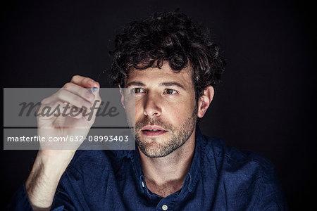 Man using stylus to write on transparent screen