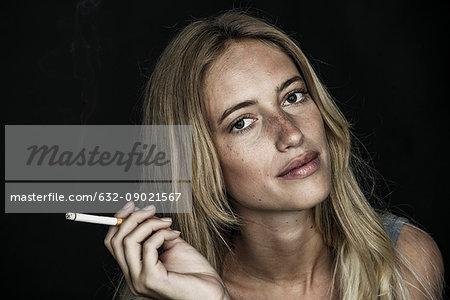 Young woman holding cigarette, portrait