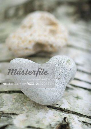 Heart shaped stones on bark background, extreme close-up