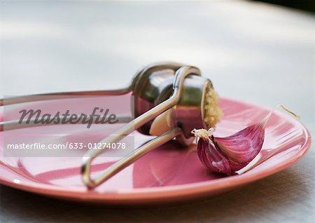Garlic press and clove of garlic on plate