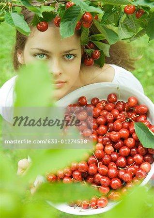 Woman holding bowl of cherries, standing under cherry tree