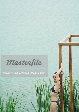Woman wearing bikini, leaning against wooden structure, near lake