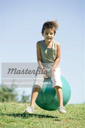 Little boy outdoors, jumping on ball, full length