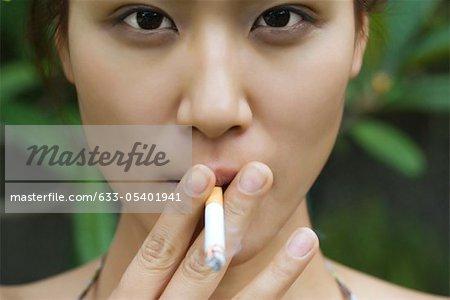 Young woman smoking outdoors