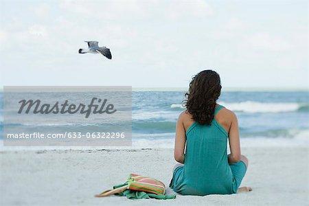 Teenage girl sitting on beach looking at ocean, rear view