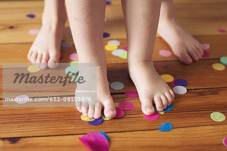 Barefeet and confetti on hardwood floor