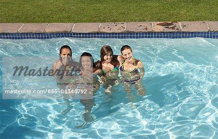 Four teenage girls in bikinis in outdoor pool