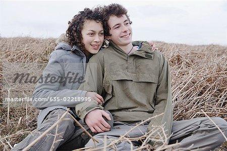 Teenage couple sitting field