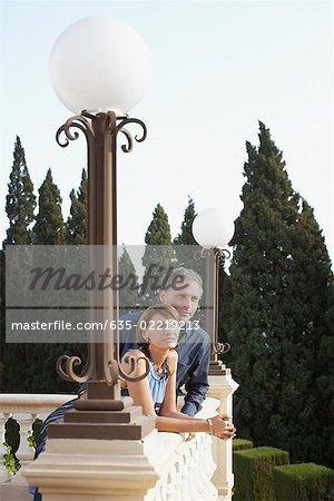 Couple leaning on balcony railing
