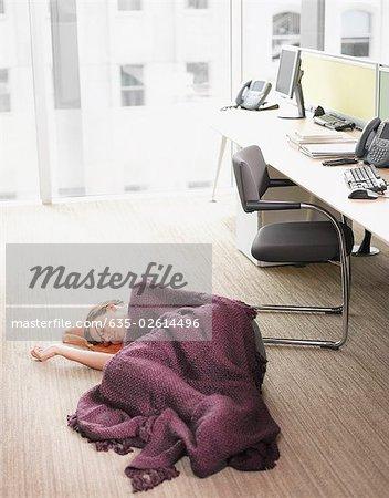 Businesswoman sleeping on office floor