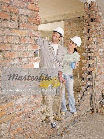 Couple standing in doorway of house under construction