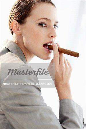 Businesswoman biting cigar