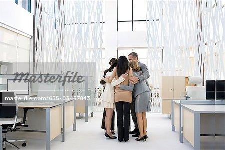 Business people huddling in modern office
