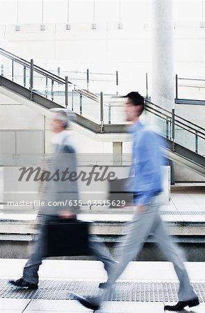 Businessmen rushing on train platform