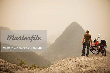 Man next to motorcycle viewing mountains