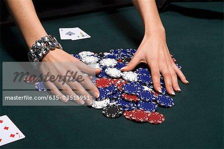 Woman gathering poker chips in casino
