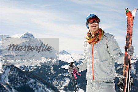 Man on mountain holding skis