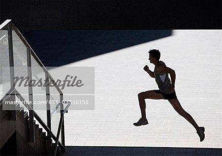 Man running towards urban staircase