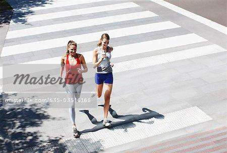 Friends running across urban crosswalk