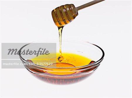 Honey dripping off honey dipper into bowl