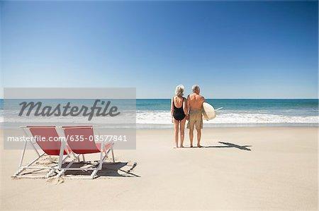 Senior couple with surfboard on beach