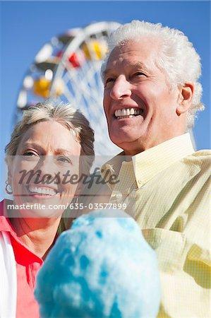 Smiling senior couple sharing cotton candy at amusement park