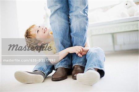 Son hugging grandfather's legs