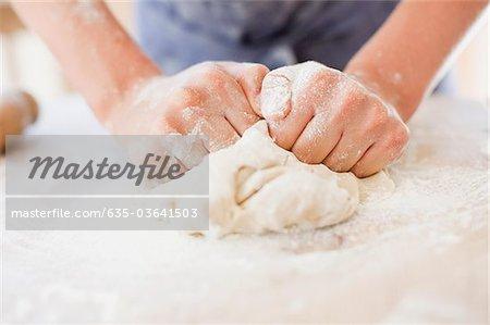 Close up of girl kneading dough