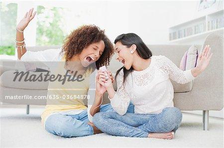 Teenage girls singing in living room